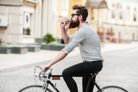 이동 커피. 젊은 수염 남자 마시는 커피의 측면보기 야외 그의 자전거에 앉아있는 동안