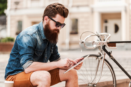 stile: Facendo un po 'di notizie. Bel giovane barbuto che tiene tabletwhile digitale seduto vicino alla sua bicicletta all'aperto