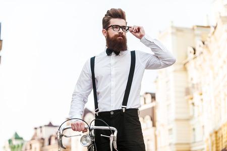 그의 완벽한 스타일에 자신감. 잘 생긴 젊은 남자의 낮은 각도보기 자전거에 기대어 야외 서있는 동안 안경을 조정 스톡 콘텐츠