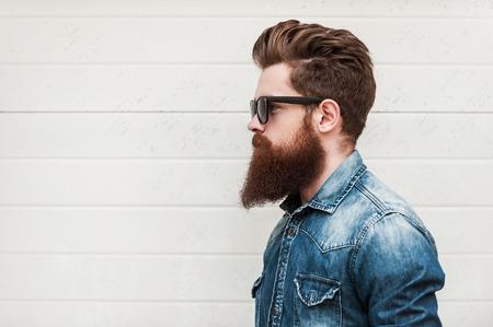 mezclilla: Estilo perfecto. Vista lateral del hombre barbudo joven en gafas mirando a otro lado mientras que de pie al aire libre