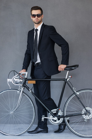 going green: Going green. Full length of handsome young businessman looking at camera and rolling his bicycle while walking against grey background Stock Photo