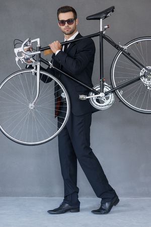 only young men: Elegant and stylish. Full length of confident young businessman carrying his bicycle on shoulder while standing against grey background Stock Photo