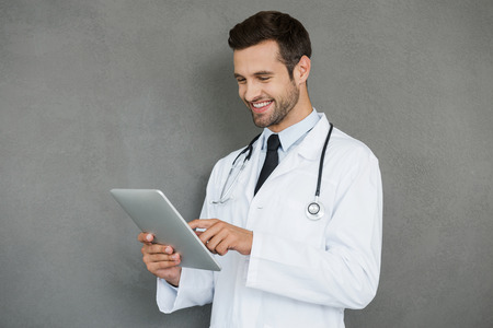 digital background: Digital solution for medical science. Smiling young doctor in white uniform working on digital tablet while standing against grey background