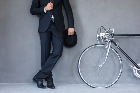 Elegant style. Close-up of young businessmanholding hat and adjusting his jacket while standing near his bicycle against grey background