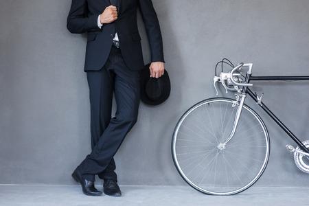 empleado de oficina: estilo elegante. Primer plano de sombrero businessmanholding joven y ajustar su chaqueta mientras está de pie cerca de su bicicleta contra fondo gris Foto de archivo