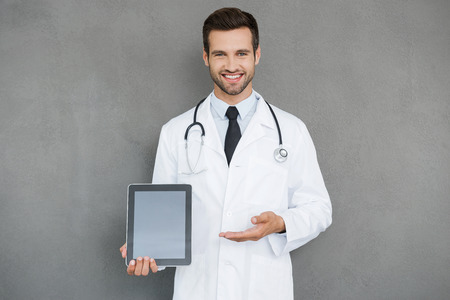 digital background: Copy space on his tablet. Cheerful young doctor in white uniform holding digital tablet and pointing at it while standing against grey background Stock Photo