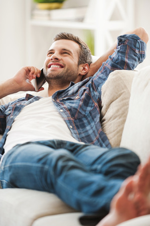 hands on head: Lazy day at home. Joyful young man talking on the phone while lying on sofa