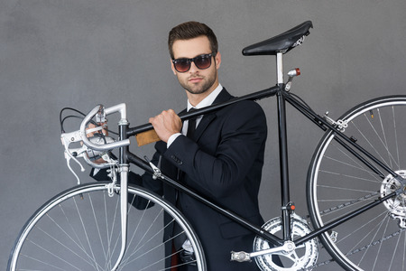 young businessman: Perfect city transportation. Confident young businessman carrying his bicycle on shoulder while standing against grey background