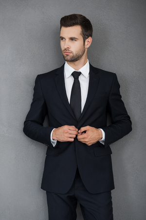 looking good: Making business looking good. Confident young businessman adjusting his jacket and looking away while standing against grey background