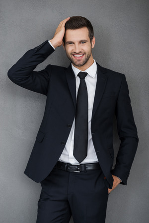 studio model: Stylish handsome. Smiling young businessman touching his hair and looking at camera while standing against grey background Stock Photo