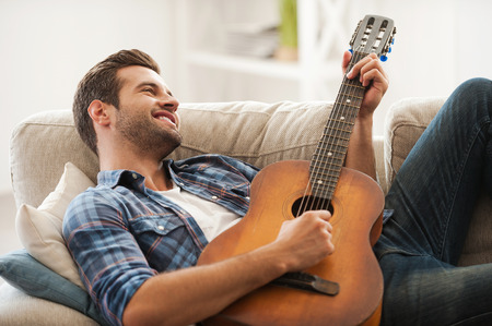 playing the guitar: Music is my life. Happy young man playing the guitar while lying on sofa Stock Photo