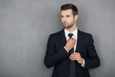 man style: Elegant and successful. Confident young businessman adjusting his necktie and looking away while standing against grey background