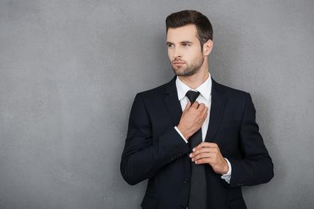 Elegante y exitosa. joven hombre de negocios confía en el ajuste de la corbata y mirando a otro lado mientras está de pie contra el fondo gris Foto de archivo - 44203271
