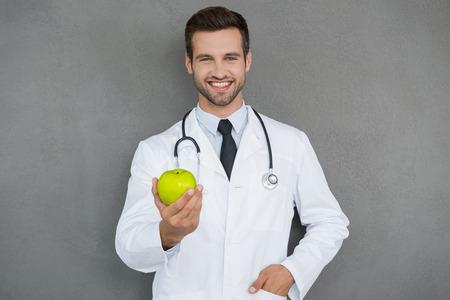 coat of arms: Las vitaminas son importantes para la salud. Doctor joven alegre en uniforme blanco estirándose manzana verde y sonriente mientras está de pie contra el fondo gris Foto de archivo