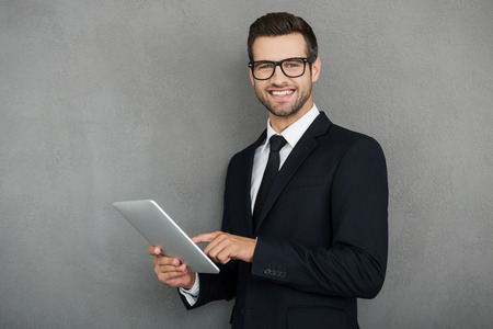 men in suit: Doing his business in easy way. Happy young businessman holding digital tablet and looking at camera while standing against grey background