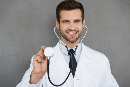 looking to camera: Let me start the exam! Smiling young doctor in white uniform wearing stethoscope and looking at camera while standing against grey background