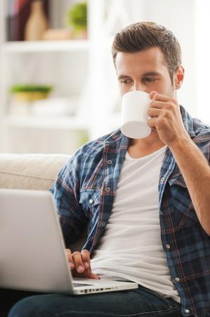tomando café: Obtener las últimas noticias en línea. Apuesto joven trabajando en la computadora portátil y el consumo de café mientras se está sentado en el sofá