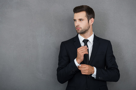 pensive man: Perfect to the last detail. Handsome young businessman adjusting his sleeves while standing against grey background