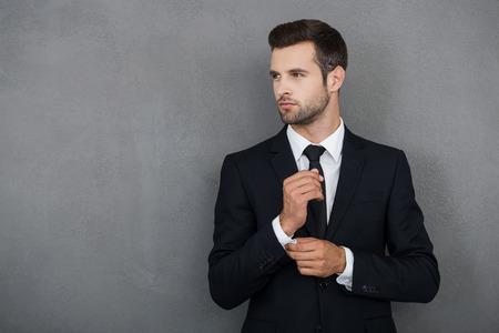 hombres guapos: Perfecto hasta el �ltimo detalle. Hombre de negocios joven hermoso que ajusta sus mangas mientras est� de pie contra el fondo gris
