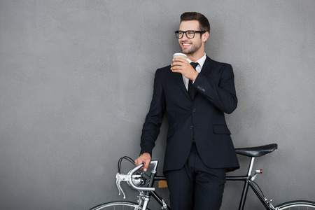 only one person: Successful businessman. Smiling young man leaning at his bicycle and holding cup of coffee while standing against grey background