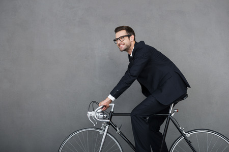 smiling businessman: Keep calm and ride on. Cheerful young businessman smiling and looking away while cycling against grey background