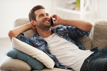 sofa: Enjoying leisure day at home. Joyful young man talking on the mobile phone and smiling while lying on sofa