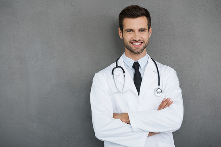 You can absolutely trust me. Confident young doctor in white uniform looking at camera and keeping arms crossed while standing against grey background Imagens
