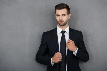 Vertrouwen in zijn volmaaktheid. Knappe jonge zakenman aanpassing van zijn jas en kijken naar de camera terwijl je tegen een grijze achtergrond