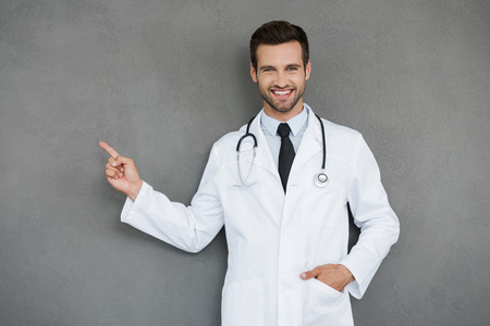 expressing positivity: Showing new ways of healing. Smiling young doctor in white uniform looking at camera and pointing away while standing against grey background
