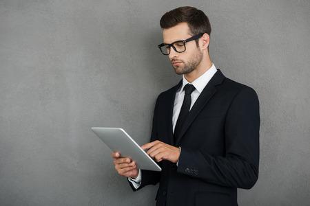オンラインの彼のメールをチェックします。灰色の背景に対して立っている間彼のデジタル タブレットに取り組んでいる深刻な青年実業家