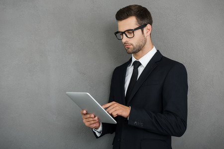 Checking his emails online. Serious young businessman working on his digital tablet while standing against grey background