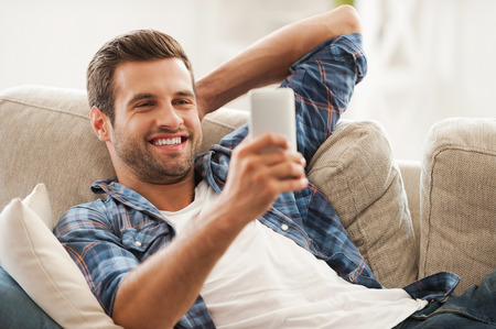 hombres jovenes: Mantenerse en contacto en casa. Hombre joven alegre que sostiene el tel�fono m�vil y sonriendo mientras est� acostado en el sof� Foto de archivo