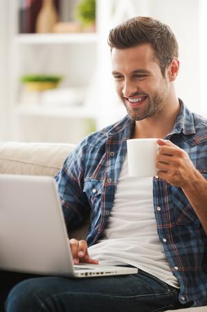 hombres trabajando: Pasar tiempo en línea. Sonriendo manworking joven en la computadora portátil y la celebración de taza de café mientras estaba sentado en el sofá