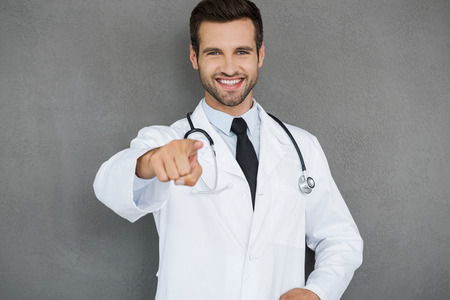 coat of arms: I will take care of your health! Cheerful young doctor in white uniform pointing at camera while standing against grey background
