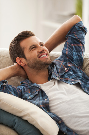 hands on head: Chill time on sofa. Joyful young man holding hands behind head and smiling while lying on sofa Stock Photo
