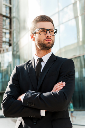 men in suit: Thinking about solutions. Low angle view of handsome young businessman keeping arms crossed and looking away while standing outdoors with office building in the background