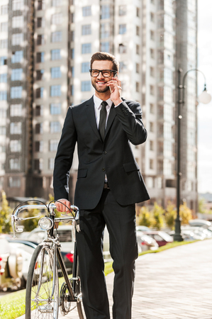 business intelligence: Business on the go. Happy young businessman rolling his bicycle and smiling while walking outdoors Stock Photo
