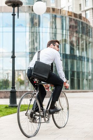 looking around: Getting around town by bike. Rear view of young businessman looking away while riding on his bicycle