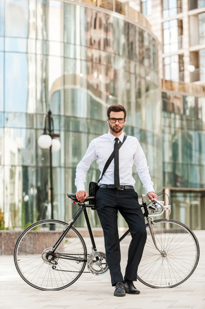 standing businessman: I choose the green way! Full length of handsome young businessman leaning at his bicycle and looking at camera while standing outdoors