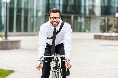 empleado de oficina: La mejor manera de llegar al trabajo. Empresario joven feliz sonriendo y mirando a la c�mara, mientras viajaba en su bicicleta