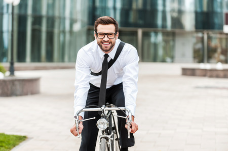 one young man: The best way to get to work. Happy young businessman smiling and looking at camera while riding on his bicycle Stock Photo