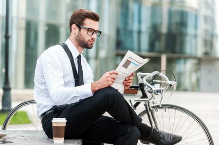 bicyclette: La lecture des derni�res nouvelles. Vue de c�t� de jeune homme d'affaires lisant le journal alors qu'il �tait assis pr�s de son v�lo avec immeuble de bureaux dans le fond