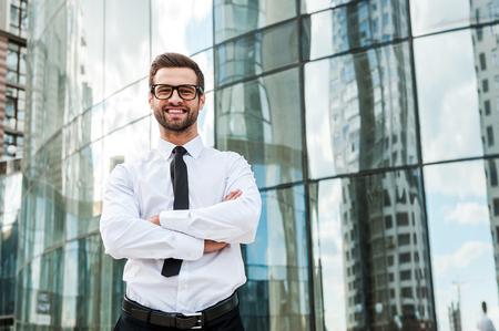 ejecutivos: Se utiliza para el éxito. Ángulo de visión baja de hombre de negocios sonriente joven que guarda los brazos cruzados y mirando a la cámara mientras está de pie al aire libre