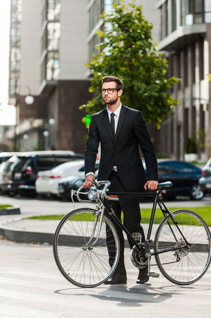 wherever: On the bike wherever I want! Full length of young businessman rolling his bicycle while crossing the road