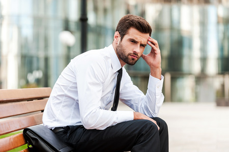 emotional stress: Too stressful day. Side view of depressed young businessman touching his forehead and looking away while sitting on the bench outdoors