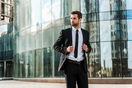 man style: Confident and successful. Handsome young businessman adjusting his jacket and looking away while walking outdoors with office building in the background