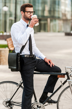 best way: The best way to start a day. Side view of handsome young businessman drinking coffee while sitting on his bicycle Stock Photo