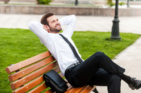 manager office: Enjoying green spaces in his city. Top view of happy young businessman keeping eyes closed and holding hands behind head while sitting on the bench outdoors