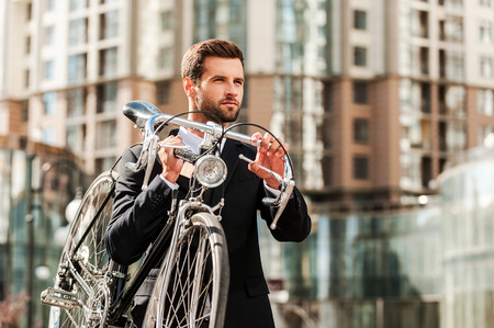 road shoulder: On the way to his work.Confident young businessman carrying his bicycle on shoulder while crossing the road