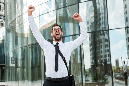 expressing: Business excitement. Cheerful young businessman keeping arms raised and expressing positivity while standing outdoors Stock Photo